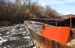 在一条河的老生锈的驳船在天 免版税库存照片