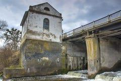 在一条河的老生锈的水坝多云天空的 图库摄影
