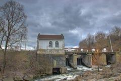 在一条河的老生锈的水坝多云天空的 库存图片
