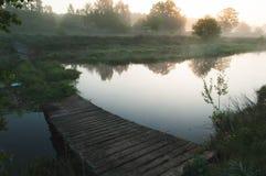 在一条河的老被毁坏的桥梁在黎明, 免版税库存照片