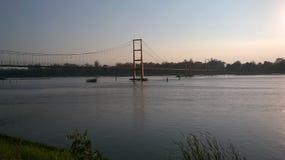 在一条河的走的桥梁日落的 免版税图库摄影