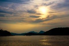 在一条河的金黄日落在蓬松云彩下 库存图片