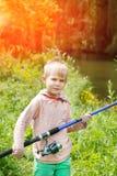 在一条河附近的逗人喜爱的小男孩立场有一根钓鱼竿的在他的手上 免版税库存图片