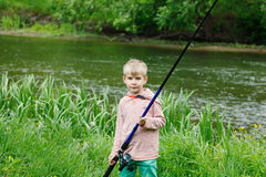 在一条河附近的逗人喜爱的小男孩立场有一根钓鱼竿的在他的手上 免版税库存照片
