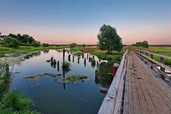 在一条沼泽的河的桥梁日落时间的 图库摄影