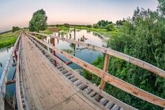 在一条沼泽的河的桥梁日落时间的 免版税库存图片