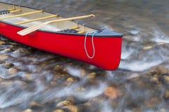 在一条浅河的红色独木舟 库存照片