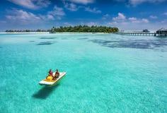 在一条浮动pedalo小船的夫妇在一个热带天堂地点 免版税库存图片