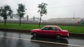 在一条湿路的红色汽车在一个雨天 库存图片