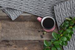 在一条灰色围巾的桃红色杯子在一张木桌上 免版税图库摄影