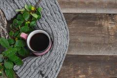 在一条灰色围巾的桃红色杯子在一张木桌上 免版税库存图片