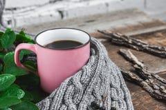 在一条灰色围巾的桃红色杯子在一张木桌上 免版税库存照片