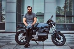 在一条灰色T恤杉和黑裤子的残酷有胡子的男性拿着一件盔甲坐他定制的减速火箭的摩托车反对 免版税图库摄影