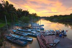 在一条热带河的美好的日出 老土气地方小船 库存图片