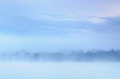 在一条狂放的河的一有薄雾的蓝色河岸的早晨 库存照片