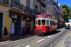 在一条狭窄的街道上的红色电车在里斯本,葡萄牙 免版税库存照片