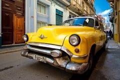 在一条狭窄的街道上的老经典美国汽车在哈瓦那旧城 免版税图库摄影