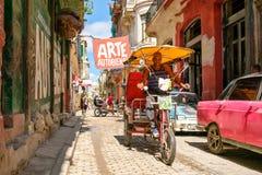 在一条狭窄的街道上的都市场面在哈瓦那旧城 库存图片