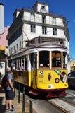 在一条狭窄的街道上的黄色电车在里斯本,葡萄牙 图库摄影
