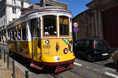 在一条狭窄的街道上的黄色电车在里斯本,葡萄牙 库存照片