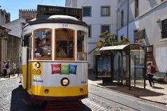 在一条狭窄的街道上的黄色电车在里斯本,葡萄牙 免版税库存照片
