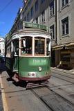 在一条狭窄的街道上的绿色电车在里斯本,葡萄牙 免版税库存图片