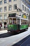 在一条狭窄的街道上的绿色电车在里斯本,葡萄牙 免版税图库摄影