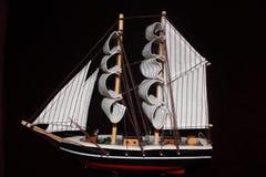在一条玩具小船的镶边风帆有船锚的 免版税库存照片