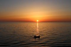在一条现出轮廓的小船里面的两个朋友在日落时间 库存照片