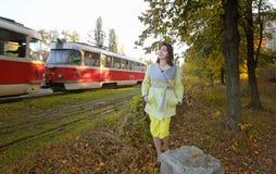 在一条电车轨道的年轻深色的身分在森林 电车附近 妇女去电车 库存图片