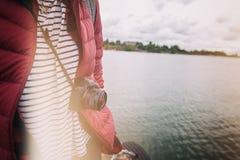 在一条皮带的一台照相机在一个风景的背景的一个人与 免版税库存照片