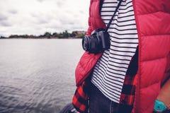 在一条皮带的一台照相机在一个风景的背景的一个人与 库存照片