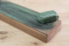 在一条皮革刀子磨剃刀用的皮带的日本皮革工艺刀子有木表面上的绿色擦亮的化合物的 库存照片
