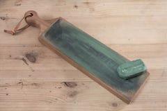 在一条皮革刀子磨剃刀用的皮带的日本皮革工艺刀子有木表面上的绿色擦亮的化合物的 库存图片