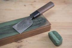 在一条皮革刀子磨剃刀用的皮带的日本皮革工艺刀子有木表面上的绿色擦亮的化合物的 免版税库存图片