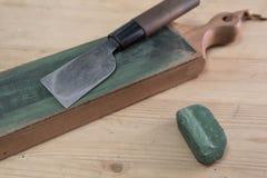 在一条皮革刀子磨剃刀用的皮带的日本皮革工艺刀子有木表面上的绿色擦亮的化合物的 图库摄影
