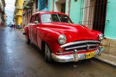 在一条破旧的街道的老红色汽车在哈瓦那 库存图片