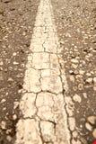 在一条破裂的柏油路的一条老空白线路 免版税库存图片
