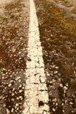 在一条破裂的柏油路的一条老空白线路 库存照片
