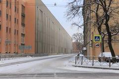 在一条离开的冬天城市街道上的暴风雪 免版税图库摄影