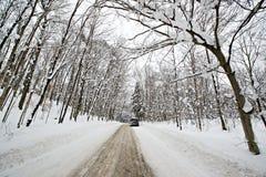 在一条积雪的农村路的汽车 免版税图库摄影