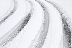 在一条积雪的路的弯曲的轮胎跟踪 库存图片