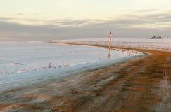 在一条积雪的路的车轮痕迹 免版税库存照片
