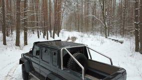 在一条积雪的路的SUV 6x6身分在冬天森林里,鸟瞰图 股票视频