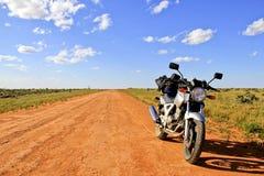 在一条空的土路在内地澳洲的摩托车 免版税库存图片