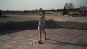 在一条空的宫殿喷泉佩带的biege夹克和五颜六色的生动的裙子-芭蕾舞女演员的疯狂的愉快的少女跳 股票录像