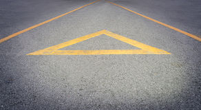 在一条粗砺的路的黄色箭头方向 库存照片
