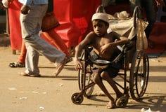在一条繁忙的路的印地安病和有残障的叫化子寻找的帮助 库存图片