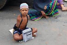 在一条繁忙的路的印地安病和有残障的叫化子寻找的帮助 免版税库存图片