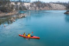 在一条红色小船的两个运动人浮游物在河 图库摄影